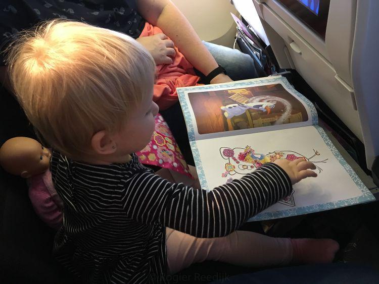 Fabienne vermaakt zich uitstekend met stickers plakken in het vliegtuig.