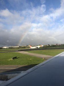 Een regenboog en landend vliegtuig van TAP op Lissabon